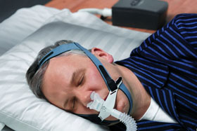 A man sleeping in bed with his cpap machine on.